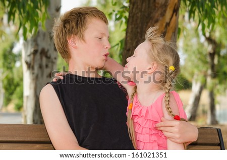 Happy childhood: two cute friends boy and girl hugging in park - stock photo