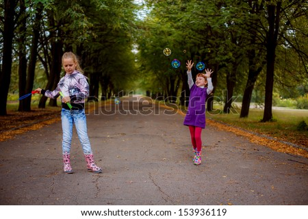 happy children allowed and catch soap bubbles - stock photo