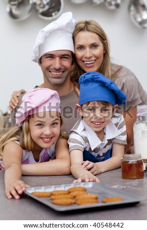Happy children and parents eating biscuits in the kitchen - stock photo