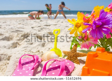 Happy children at play on the beach - stock photo