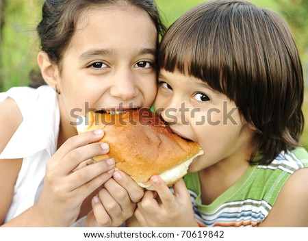 Happy children, boy and girl, eating together and smiling, nature, love and togetherness - stock photo