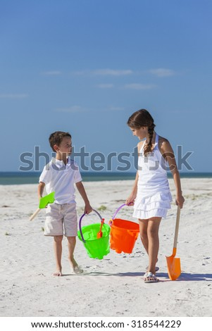 Happy children, boy girl, brother and sister having fun walking and playing in the sand on a beach with bucket and spade - stock photo