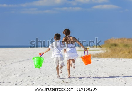 Happy children, boy girl, brother and sister running and having fun playing in the sand on a beach with bucket and spade - stock photo