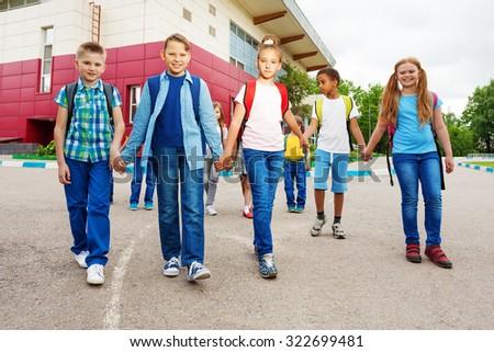 Happy children carry rucksacks, walk near school - stock photo