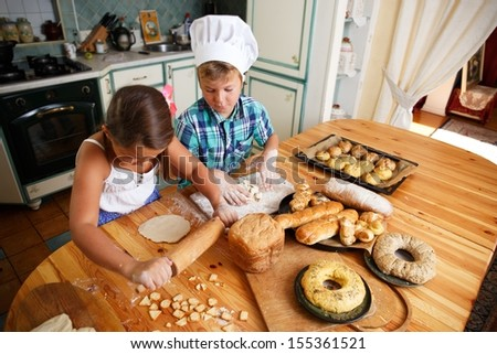 Happy children cooking homemade pastry - stock photo