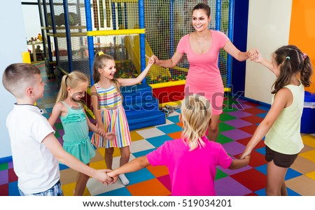 happy children dancing with teacher to music in class at school