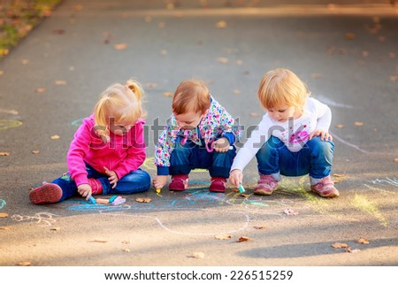 happy children draw colored chalk   - stock photo