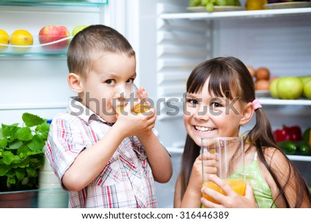 Happy children drink orange juice standing near refrigerator with fruits and vegetables