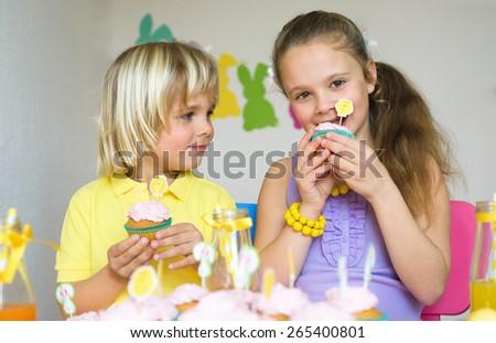 Happy children eating cupcakes in Easter scene - stock photo