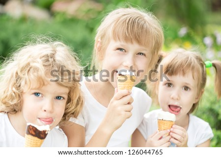 Happy children eating ice-cream outdoors in park - stock photo