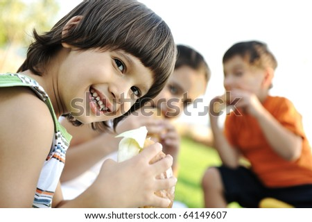 Happy children eating together in nature - stock photo
