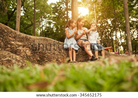Happy children enjoying ice-cream cones in the park - stock photo