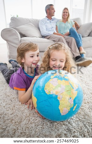Happy children exploring globe while parents sitting on sofa at home - stock photo