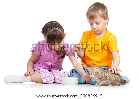happy children feeding cat kitten - stock photo