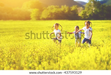 happy children friends sisters run and play outdoors on the meadow - stock photo