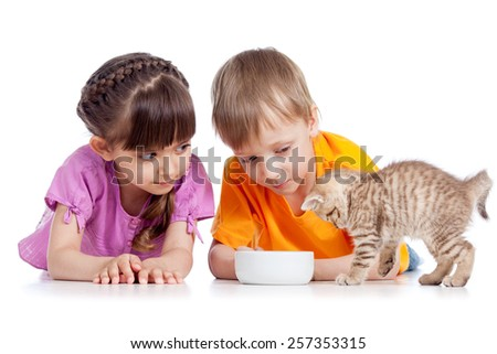 happy children girl and boy feed cat kitten - stock photo