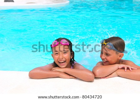 Happy children,  girl and boy, relaxing on the side of a swimming pool wearing pink and grey goggles