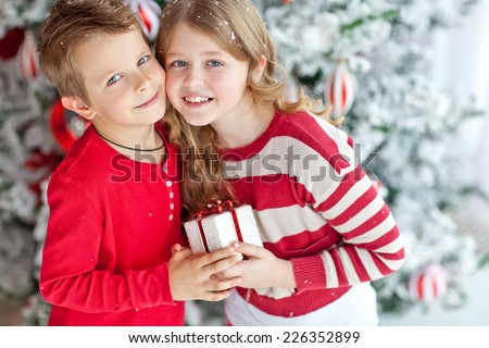 Happy children give a Christmas gift. Christmas concept. - stock photo
