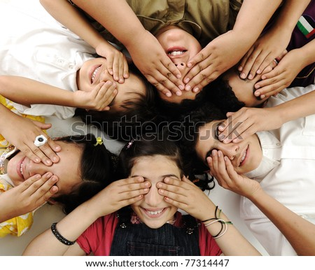 happy children group  lying and closing eyes by hands - stock photo