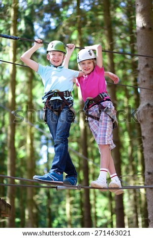 Happy children having fun in adventure park. Two adventurous healthy teenage boys, twin brothers enjoying active day outdoors climbing on the trees. Friendship and brotherhood concept. - stock photo
