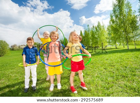 Happy children holding hula hoops during exercises - stock photo