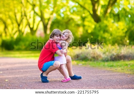 Happy children hugging and playing in a park, laughing boy and his funny curly toddler sister, adorable little girl having fun in a sunny autumn park - stock photo