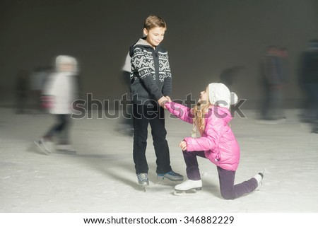 Happy children ice skating at ice rink outdoor, at winter snowy night. Brother helps for his sister. Sport and healthy lifestyle, ice skating at Holland. Funny kids, boy and girl. Family