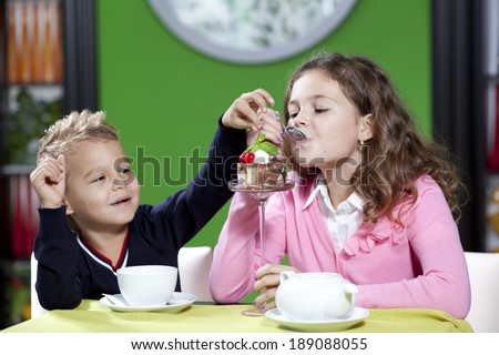Happy children in cafe.The little boy and his elder sister - stock photo