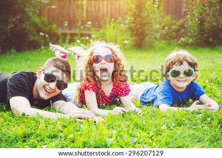 Happy children in glasses lying on the grass. Happy family concept.  - stock photo