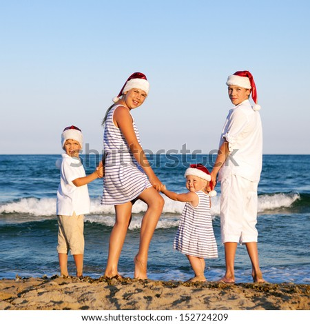 HAppy Children in santa claus hat  are standing on beach, outdoor - stock photo