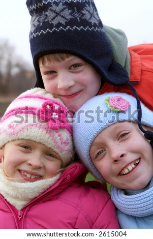 Happy children in winter outfit  on a background of field