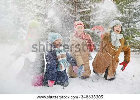 Happy children in winter-wear playing snowballs in park - stock photo