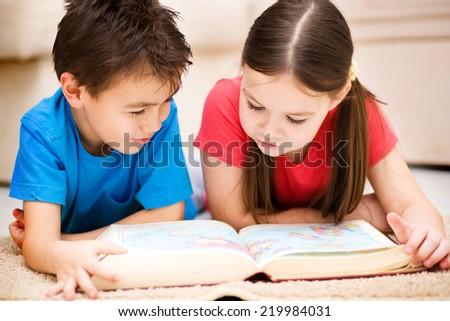Happy children is reading book - stock photo