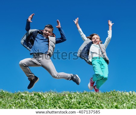 Happy children jumping on grass hill with clear blue sky - stock photo