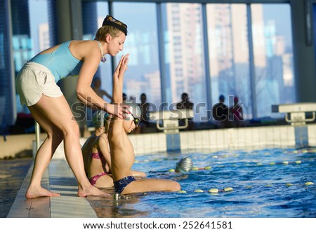 happy children kids group at swimming pool class learning to swim - stock photo