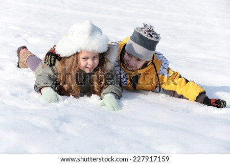 Happy children laying down in the snow   - stock photo