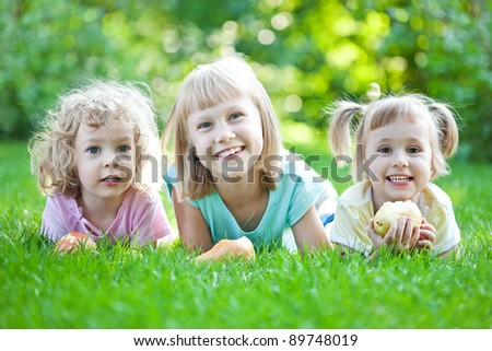 Happy children laying on grass. Family picnic in spring park - stock photo