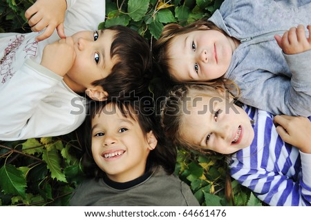 Happy children laying together in circle on ground - stock photo