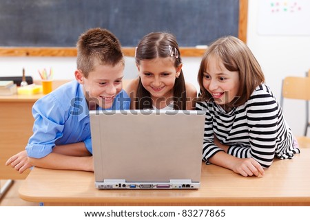 Happy children looking at laptop computer, surfing interesting content on the internet