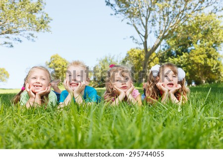 Happy children lying at park - stock photo