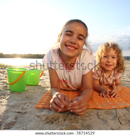 Happy children lying on beach