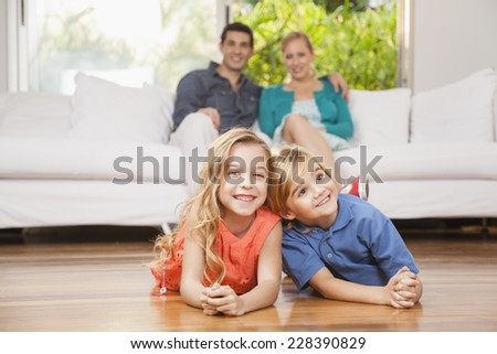 Happy children lying on floor, parents sitting on couch in background - stock photo