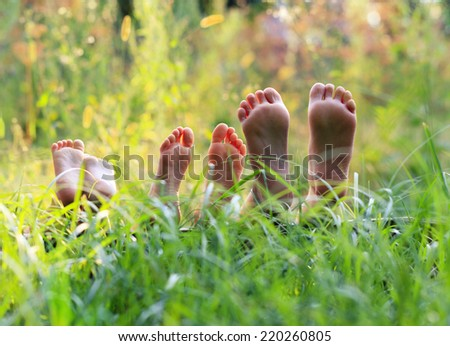 Happy children lying on green grass  - stock photo