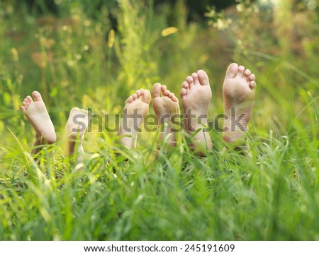 Happy children lying on green grass  - stock photo