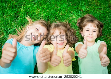 Happy children lying on green grass in spring park. Laughing kids showing thumbs up - stock photo