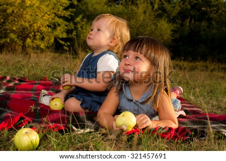 happy children lying on green grass outdoors in spring park with apples