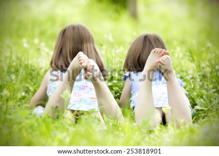 Happy children lying on green grass outdoors in the grass - stock photo