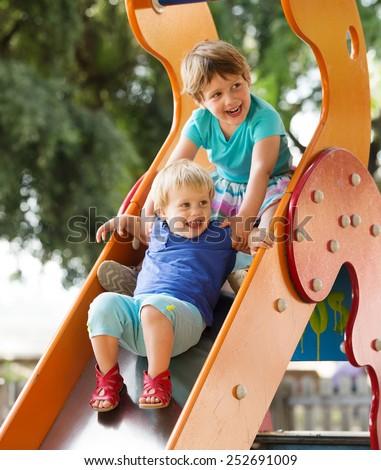 happy children on slide  in summer - stock photo