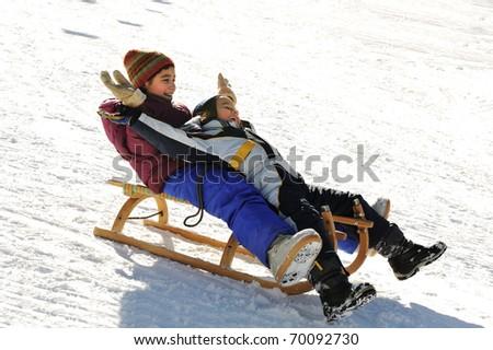 Happy children on snow - stock photo
