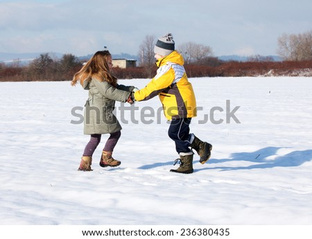 Happy children play down in the snow - stock photo